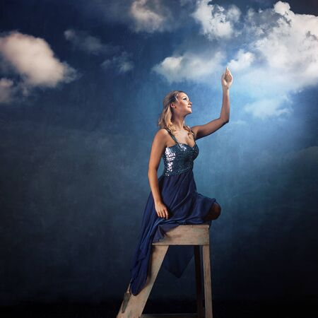 girl on the ladder reaches up with her hands. A young woman in a blue dress on a blue background dreams and stretches her hands to the clouds Foto de archivo