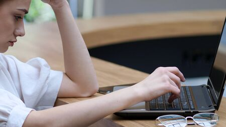 Freelancing and remote work. Young woman with glasses typing a letter on a laptop, close- up