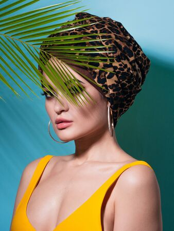 An attractive young woman in a stylish turban made of leopard print fabric on a blue background. Girl with bright makeup. Beach style, palm branch and heat