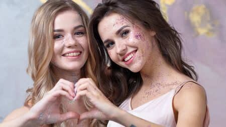 Blonde and brunette with light makeup with added glitter. Shine in an everyday way. Happy smiling girlfriends Standard-Bild