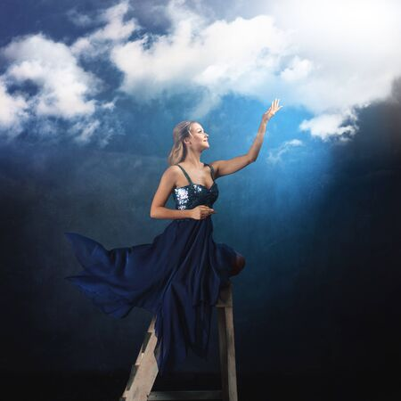 girl on the ladder reaches up with her hands. A young woman in a blue dress on a blue background stretches her hands to the clouds, dreamers concept