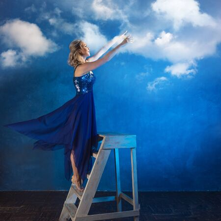 girl on the ladder reaches up with her hands. A young woman in a blue dress on a blue background dreams and stretches her hands to the clouds 版權商用圖片