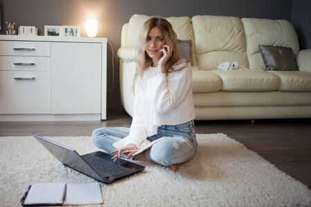 Work from home, remote work, and freelance. A young woman in a white sweater is sitting on the carpet with a laptop and a phone. The girl is on the phone sitting on the floor