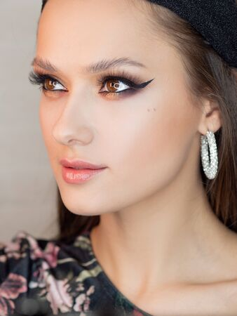 Portrait of a young beautiful brunette woman with bright eye makeup. Image of a southern beauty with earrings rings