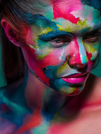 Multicolored skin, difficult to identify. Creative makeup with colorful patterns on the face. Fake face vs face identification and surveillance