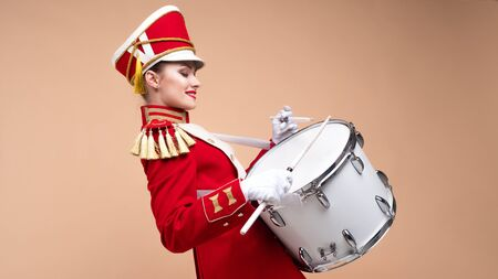 Charming cheerful drummer in a red uniform, sings and plays the drum. Beige background with copy space