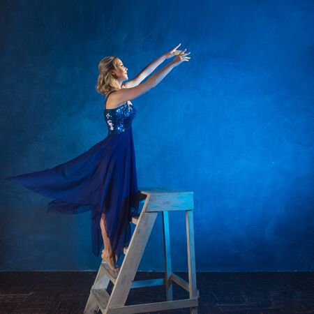girl on a stepladder reaches up with her hands, dreaming and wanting