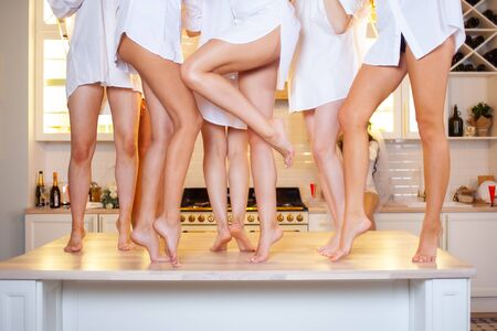 Women's legs, smooth skin and well-groomed feet, depilation and pedicure. Group of girlfriends with beautiful legs dancing on the table, women's party