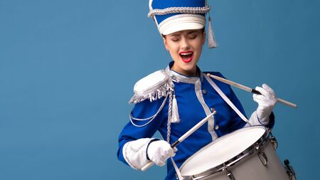 Charming cheerful drummer in a blue uniform, sings and plays the drum. Blue background copy space Foto de archivo