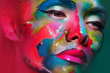 Face art and body art. Creative makeup with colorful patterns on the face. Modern makeup art, bold style, close-up portrait of a woman