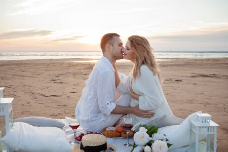 Picnic at sunset. A man and a pregnant woman sit on a bedspread, among fruits and pillows, on the beach, hugging, kissing against the backdrop of low tide and a wide coastal strip.