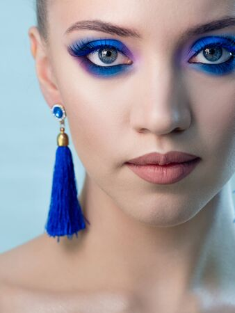 Glamorous bright eye makeup using the trend color classic blue, women's eyes close-up. One tone look with tassel earrings