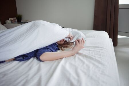 Morning, the woman under the blanket, turns off the alarm clock or watching the social network
