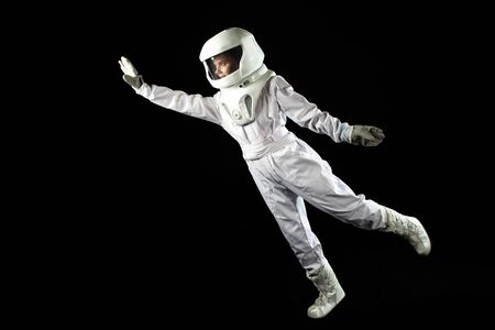 Astronaut in space, in zero gravity on black background.