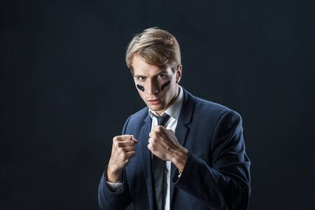 young man in a business suit rolled up his sleeves and Boxing. Aggressive business, concept. Businessman with war paint on his face