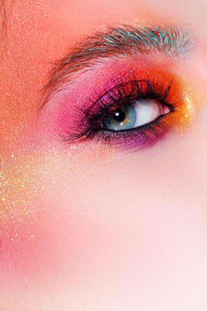 Bright makeup and face art, close-up of the eye. Bright pink eye shadow and glitter. Eyebrows and lashes, bright eye makeup
