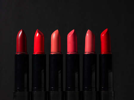 set of six multi-colored lipsticks or lip glosses. set of makeup artist, beauty and cosmetics for every day, black background Archivio Fotografico