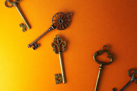Many different old keys from different locks, scattered chaotically, flat lay. Finding the right key, encryption, concept. Retro vintage copper keys in bright orange background