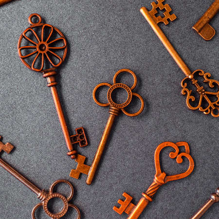 Many different old keys from different locks, scattered chaotically, flat lay. Finding the right key, encryption, concept. Retro vintage copper keys on grey background