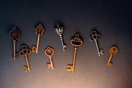 Many different old keys from different locks, scattered chaotically, flat lay. Finding the right key, encryption, concept. Retro vintage copper keys in black background, mystical light from below