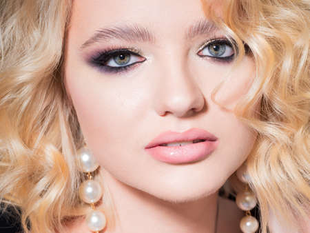 Gorgeous blonde, portrait on a black background. Beautiful young girl with stylish sexy make-up, face close-up. A young woman with a stylish hairstyle and pearl earrings