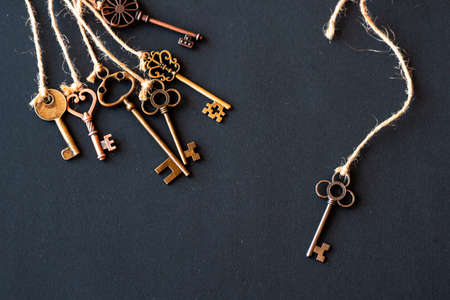 A bunch of different old keys from different locks. Finding the right key, encryption, concept. Retro vintage copper keys tied with rough rope, dark background