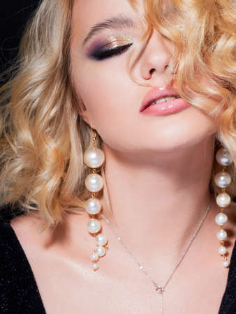 Gorgeous blonde, portrait on a black background. Beautiful young girl, makeup for the celebration. A young woman with a stylish hairstyle and pearl earrings