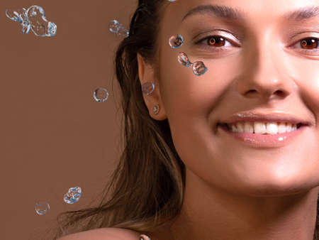 Refresh your face, wash with clean water, concept. A splash of water and a portrait of a young beautiful woman, skin care, facial cleansing. Tanned cute girl enjoys washing her face