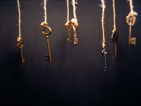 A lot of different old keys from different locks, hanging from the top on strings. Finding the right key, encryption, concept. Retro vintage brass keys on a dark background Imagens