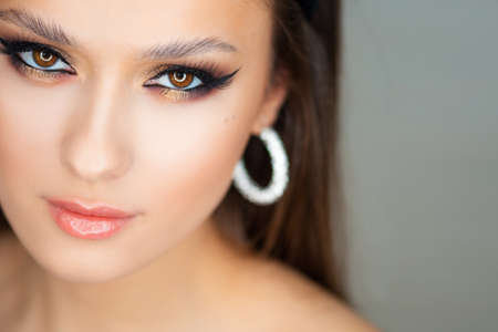 Portrait of a young beautiful brunette woman with bright eye makeup. Image of a southern beauty with earrings rings. Close-up, looking at the camera Stok Fotoğraf