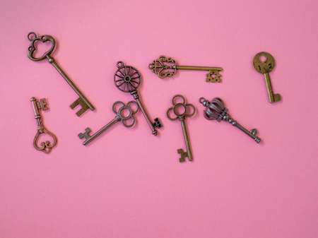 Many different old keys from different locks, scattered chaotically, flat lay. Finding the right key, encryption, concept. Retro vintage copper keys on a pink background