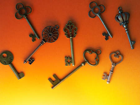 Many different old keys from different locks, scattered chaotically, flat lay. Finding right key, encryption, concept. Retro vintage copper keys in bright orange background, mystical light from below