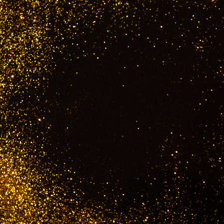 Sparkling gold glitter on a black background, magic abstract background. Round frame made of gold particles, copy space in the center, template for greeting or lettering Foto de archivo