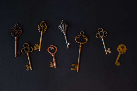 Many different old keys from different locks, scattered chaotically, flat lay. Finding the right key, encryption, concept. Retro vintage copper keys in black background