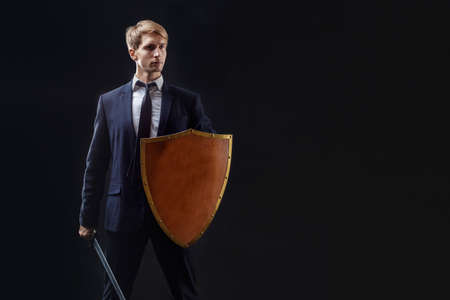 Manager with shield and sword protects business, the concept of crisis management. Protective barrier, protector