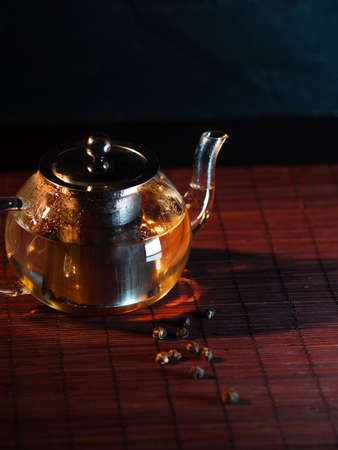 Black tea in a glass teapot. Freshly brewed tea, delicious and healthy hot drink. Hot drink on Mat, dark still life