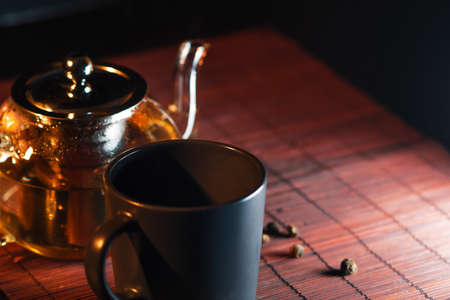 Black tea in a glass teapot. Freshly brewed tea, delicious and healthy hot drink. Hot drink on Mat, dark still life Stock fotó - 154842048