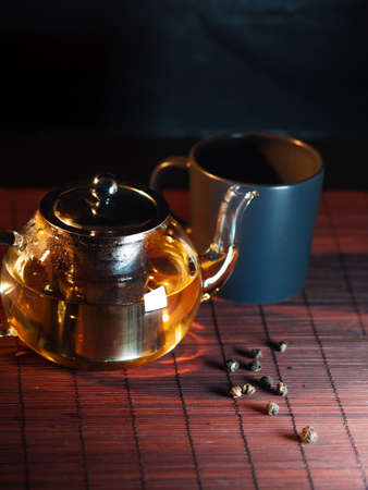 Black tea in a glass teapot. Freshly brewed tea, delicious and healthy hot drink. Hot drink on Mat, dark still life Stock fotó - 154842243