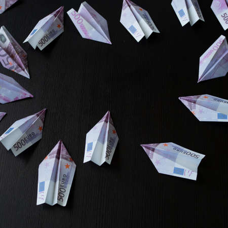 Paper airplanes made of Euro banknotes, the concept of cash flow. Inflation and problems in the economy, money flies away for spending.