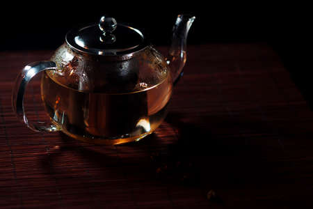 Black tea in a glass teapot. Freshly brewed tea, delicious and healthy hot drink. Hot drink on Mat, dark still life Stock fotó - 154842339