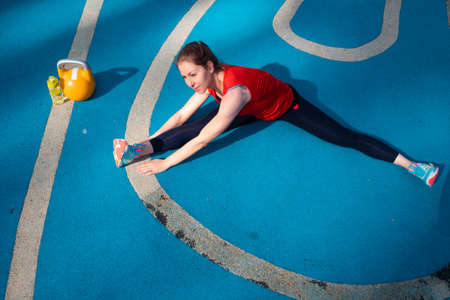 positive young woman goes in for sports. Do stretching and splits. Young female athlete doing workout, training with a kettlebell in the open air. Stok Fotoğraf