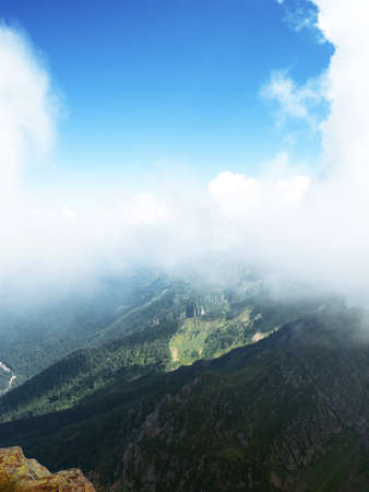 At the top, beautiful wild nature. High-mountain massif, clouds over mountain peaks. slope in the foreground, a mountain range going into perspective, in the clouds.