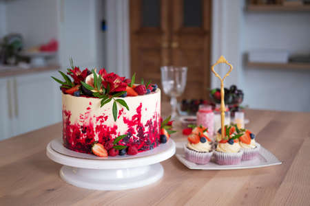 Big beautiful red velvet cake, with flowers and berries on top. Delicious sweet muffins with cream, decorated with strawberries and blueberries. Desserts on the kitchen table Standard-Bild