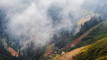 Mountain resort in summer, beautiful landscape, green valley between mountain peaks. Infrastructure for traveling in the mountains. Chair lift. Cable car in the clouds.