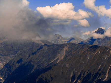 Beautiful mountain landscape. High-mountain massif, clouds over mountain peaks. Harsh mountain peaks in the clouds, the power of nature