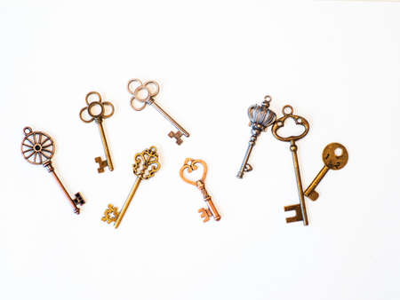Many different old keys from different locks, scattered chaotically, flat lay. Finding the right key, encryption, concept. Retro vintage copper keys in white background