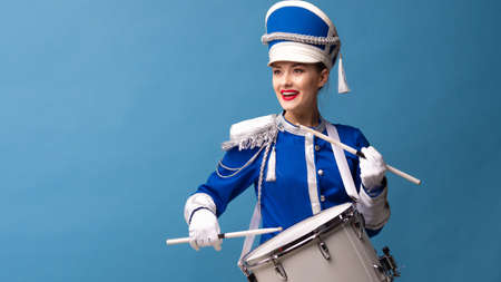 drummer in a blue uniform drums on a drum, show program and celebration. Funny drummer plays drums and sings, joy and celebration Фото со стока