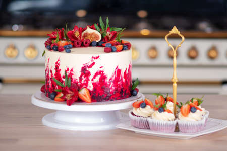 Big beautiful red velvet cake, with flowers and berries on top. Delicious sweet muffins with cream, decorated with strawberries and blueberries. Desserts on the kitchen table