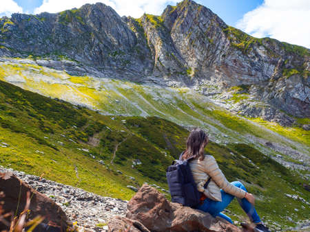 Rest and relaxation alone with nature in the mountains. Young female tourist traveling in the mountains, sitting on a rock, looking ahead to the horizon