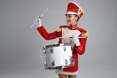 drummer in a red uniform drums on a drum, show program and celebration. Funny drummer plays drums and sings, joy and celebration